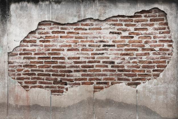 Tijolos de grunge em uma parede de concreto rachada com plano de fundo texturizado