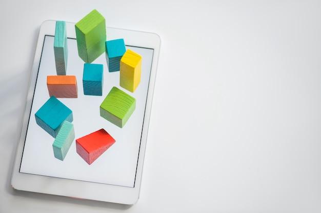 Tijolos e cubos planos de madeira azuis, laranja e verdes que compõem o gráfico na tela do tablet com copyspace à direita