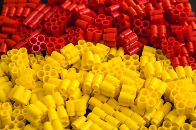 Tijolos plásticos de amarelo e vermelho em um fundo preto. detalhes dos brinquedos. fechar-se