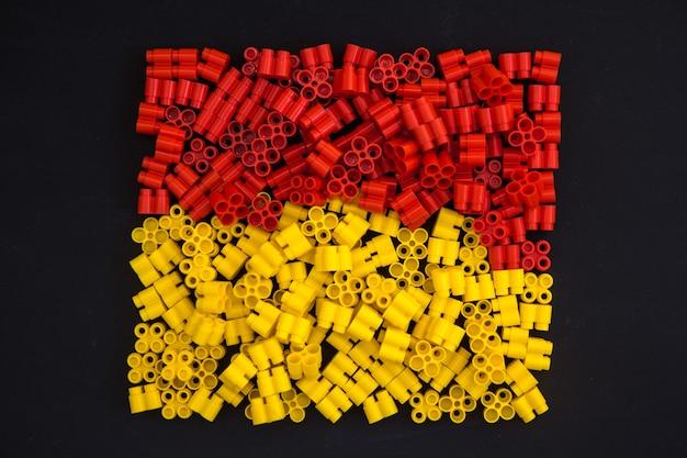 Tijolos plásticos de amarelo e vermelho em um fundo preto. detalhes dos brinquedos. vista do topo.