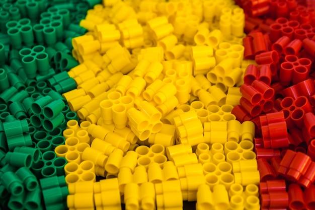 Tijolos plásticos de vermelho, amarelo e verde. detalhes dos brinquedos. fechar-se.