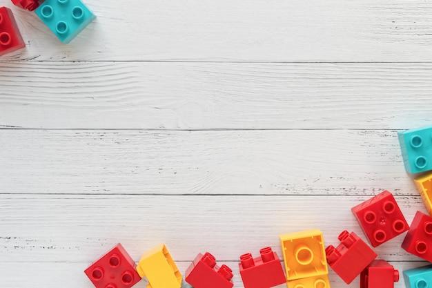 Tijolos plásticos do construtor no fundo de madeira branco. brinquedos populares. espaço livre para o texto