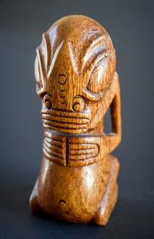 Tiki polinésio tradicional de madeira das ilhas marquesas. isolado em um fundo escuro