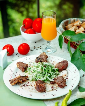 Tikka kebab com pão sírio, cebola, ervas e sumagre