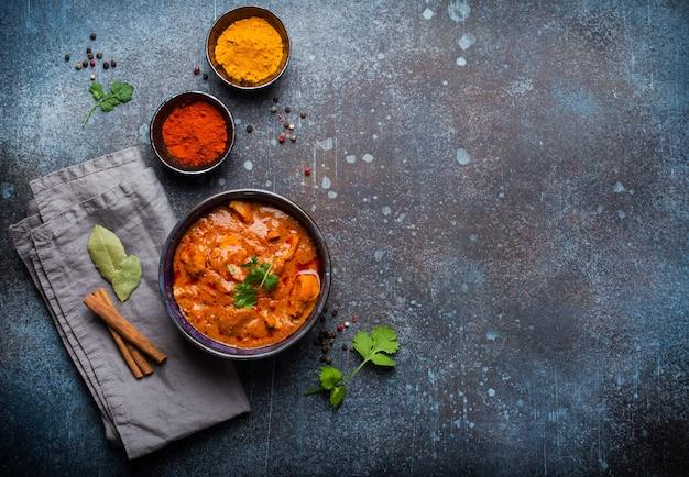Tikka masala de frango com caril picante servido em uma tigela de cerâmica rústica, prato indiano popular, em fundo de concreto, vista superior e espaço para texto