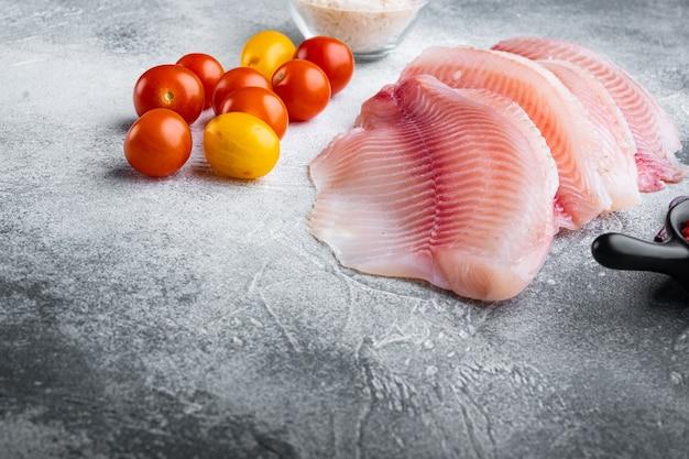 Tilápia de peixe branco cru, com ingredientes de arroz basmati e tomate cereja, em fundo cinza com espaço de cópia para o texto