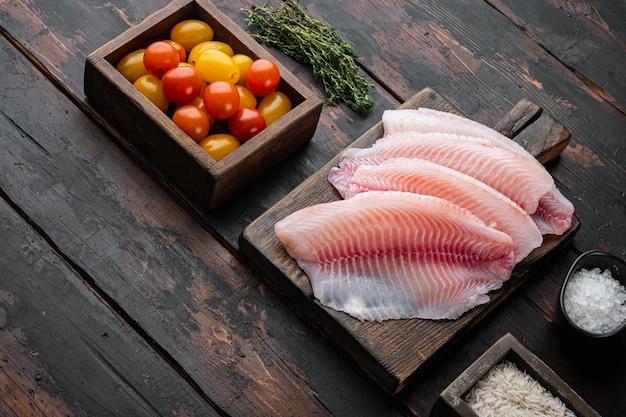Tilápia de peixe branco cru, com ingredientes de arroz basmati e tomate cereja, em fundo escuro de madeira com espaço de cópia para o texto
