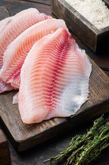 Tilápia de peixe branco cru, com ingredientes de arroz basmati e tomate cereja, em mesa de madeira escura