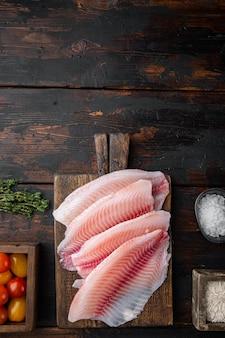 Tilápia de peixe branco cru, com ingredientes de arroz basmati e tomate cereja, na mesa de madeira escura, vista superior