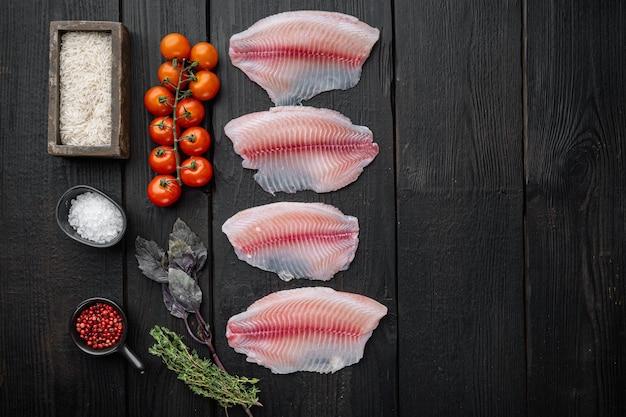 Tilápia de peixe branco cru, com ingredientes de arroz basmati e tomate cereja, na mesa de madeira preta, vista superior