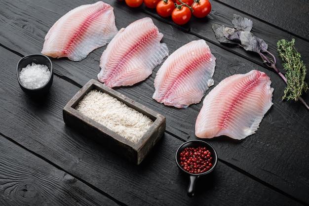 Tilápia de peixe branco cru, com ingredientes de arroz basmati e tomate cereja, na mesa de madeira preta