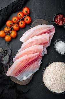 Tilápia de peixe branco cru, com ingredientes de arroz basmati e tomate cereja, na mesa preta, vista superior