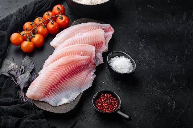 Tilápia de peixe branco cru, com ingredientes de arroz basmati e tomate cereja, na mesa preta