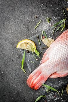 Tilápia de peixe cru vermelho sobre uma tábua sobre uma mesa de pedra preta, com especiarias, limão e ervas