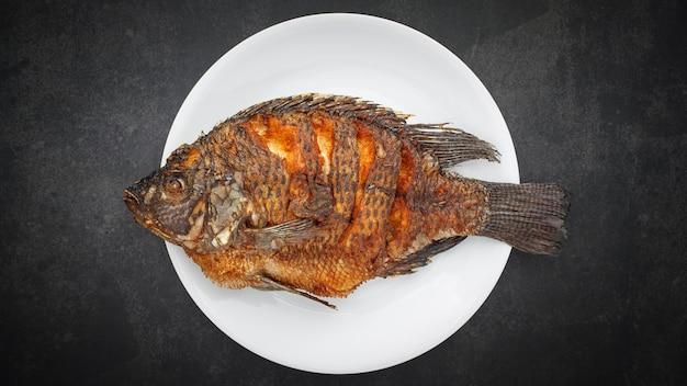 Tilápia do nilo frita com prato branco simples