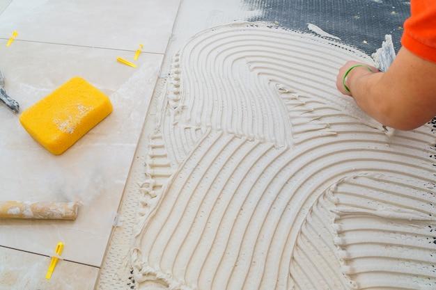 Tiler e gesso reparar o trabalho colocando a telha, colher de pedreiro em uma mão de homem