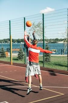 Time de basquete. homens simpáticos e simpáticos jogando a bola uns para os outros enquanto praticam basquete