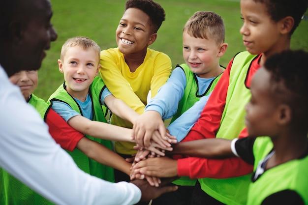 Time de futebol júnior empilhando as mãos antes de uma partida