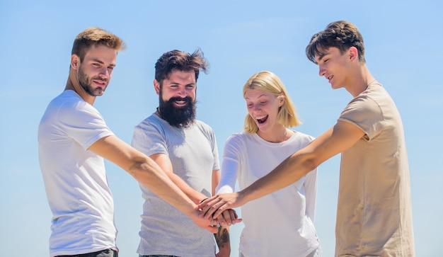 Time dos sonhos. membro da comunidade. rapazes e raparigas alegres. grupo de quatro pessoas. conceito de parceria. comunicação em grupo. pessoas unidas. parceiros da equipe. espírito de equipe. trabalho em equipe e objetivos. alcance o sucesso.