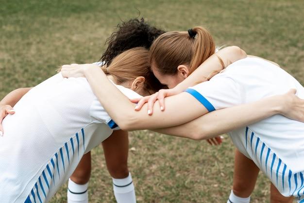 Time feminino se abraçando ao ar livre