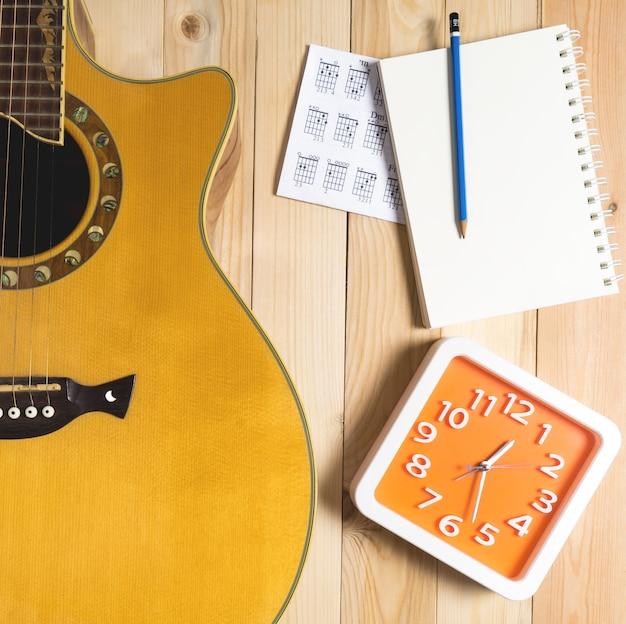 Time for guitar song writing com um relógio vermelho.