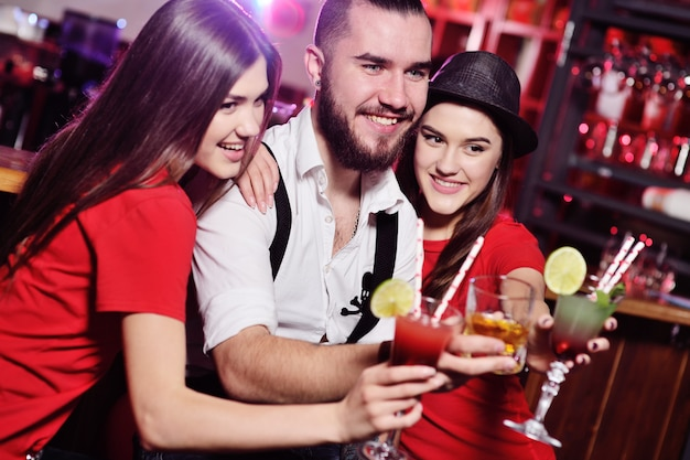 Time selfie. um grupo de amigos em uma festa em uma boate tilintar de copos com bebidas alcoólicas. jovens felizes com cocktails no bar.
