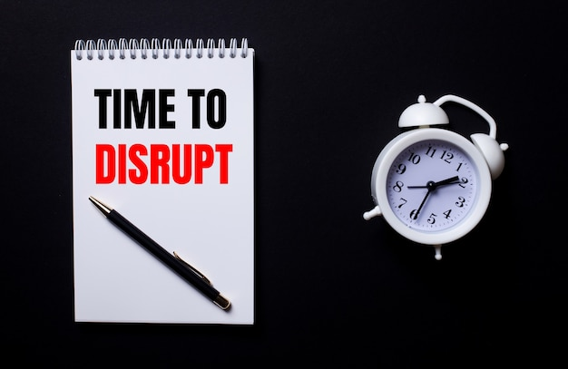 Time to disrupt está escrito em um bloco de notas branco perto de um despertador branco em um fundo preto