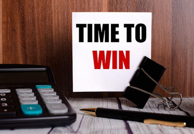 Time to win está escrito em um cartão branco em uma parede de madeira ao lado de uma calculadora e caneta.
