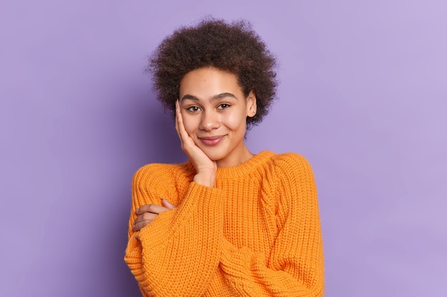 Tímida bonita adolescente com cabelo encaracolado mantém a mão na bochecha sorri suavemente, estando de bom humor, usa um macacão de malha casual.