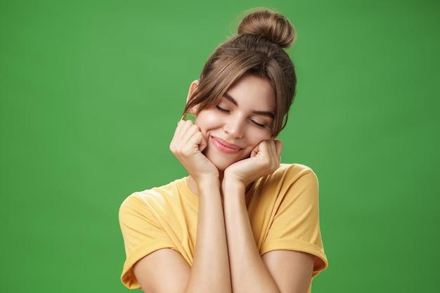 Tímida e sensual garota europeia tímida em camiseta amarela, inclinando a cabeça no ombro, tocando as bochechas com as mãos fechando os olhos e sorrindo com um sorriso suave, sentindo-se nostálgica e romântica sobre a parede verde.