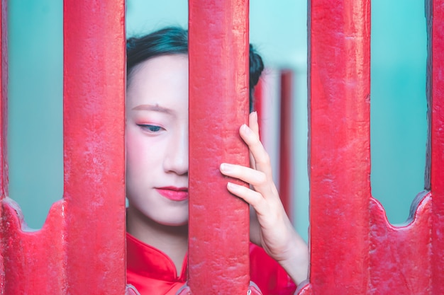 Tímida mulher chinesa está se escondendo atrás da porta de madeira vermelha