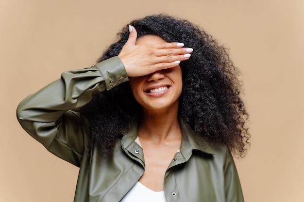 Tímida mulher encaracolada com cabelos luminosos e roupas casuais