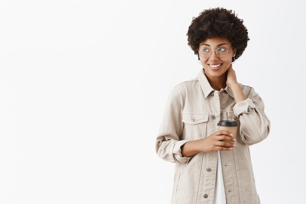 Tímida trabalhadora de escritório afro-americana com camiseta e óculos tocando o pescoço, olhando para a esquerda com um sorriso e segurando o copo de papel