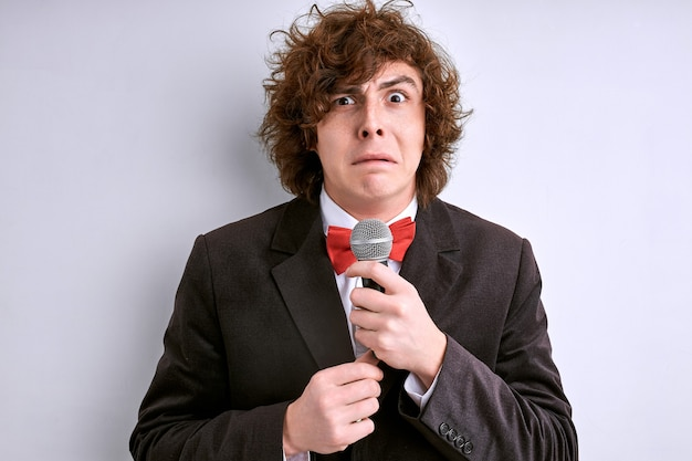 Tímido orador público masculino com microfone isolado na parede branca. cara encaracolado tem medo de fazer um discurso para uma multidão de pessoas ou audiência