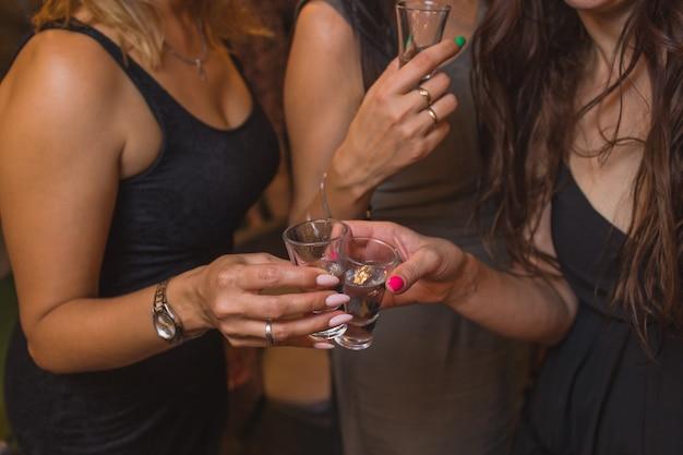 Tinir copos com álcool e brindar, festa.