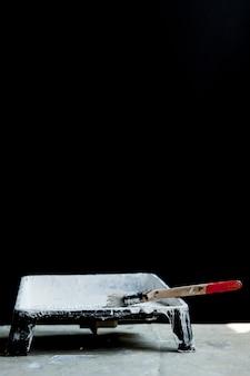Tinta branca, pincel e bandeja, para pintura de teto ou acabamento branco