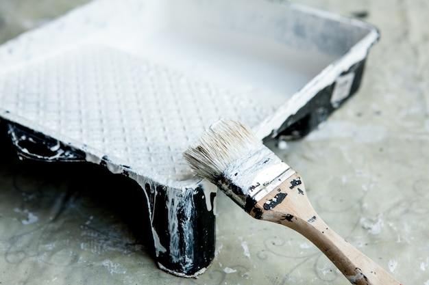 Tinta branca, pincel e bandeja, para pintura de teto ou acabamento branco.