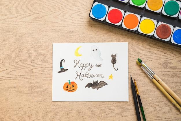 Tinta e pincéis perto de desenho de halloween Foto gratuita