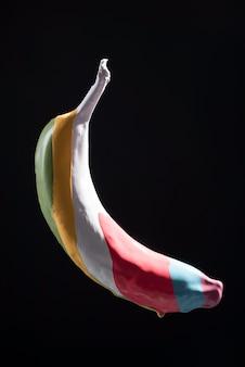 Tinta multicolorida em listras de banana, levitação de banana multicolorida em fundo preto.
