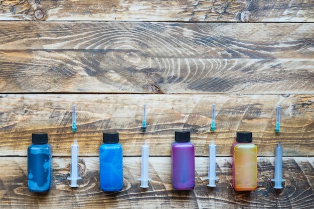Tinta para seringas de impressora em fundo de madeira