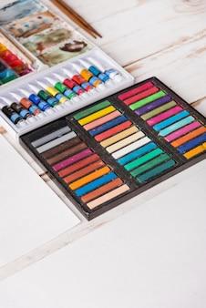 Tinta pastel e aquarela em caixas na mesa de madeira branca