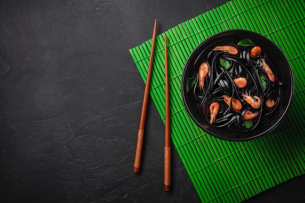 Tinta preta de lulas fettuccine com camarões ou camarões, salsa, chili com molho de vinho e manteiga.