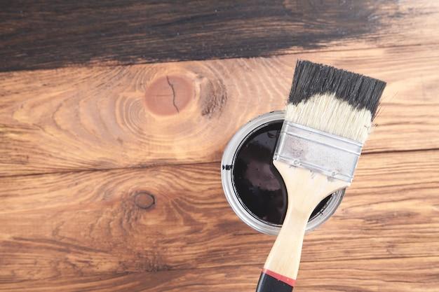 Tinta preta e pincel em fundo de madeira.