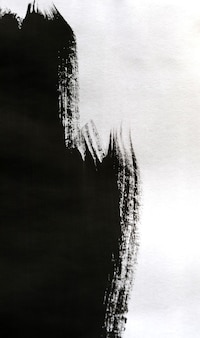 Tinta preta transportada sobre papel branco de close-up. fundo abstrato isolado no fundo branco. manchas de tinta se espalham e são absorvidas pela macro do papel.