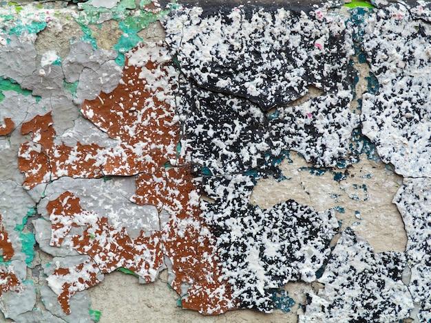 Tinta verde e marrom no gesso rachado. parede em ruínas com salpicos de tinta multi-coloridas