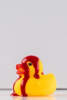 Tinta vermelha em pato de borracha amarelo