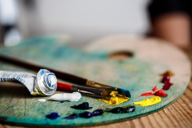 Tintas a óleo e pincéis na paleta sobre parede de madeira
