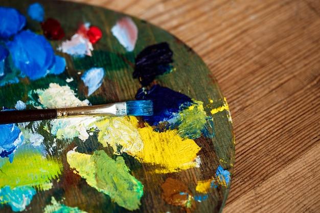 Tintas a óleo e pincel na paleta sobre parede de madeira