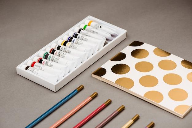Tintas a óleo, lápis e caderno na mesa cinza