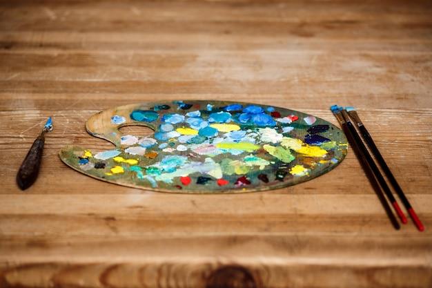 Tintas a óleo na paleta e pincéis sobre parede de madeira